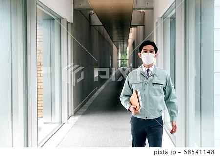 オフィスの廊下を歩くマスク姿の作業服を着たビジネスマン 68541148