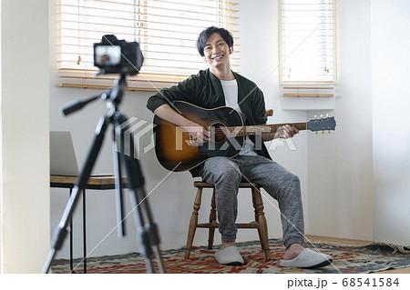 ギターを持って動画撮影をする男性 ライブ配信をするミュージシャン イメージ 68541584