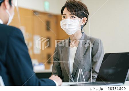 感染防止対策を講じた対面での説明シーン 68581899