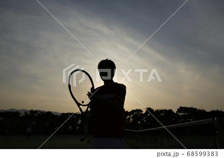 夕方にテニスのラケットを持つ選手 68599383