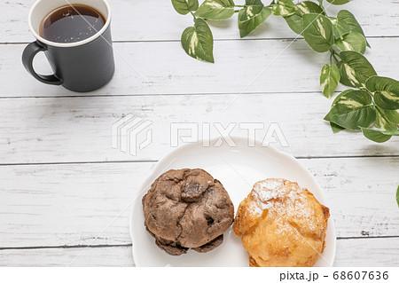 コーヒーカップと白い皿にのせた2種類のシュークリーム 68607636