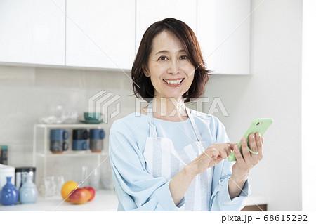 キッチンでスマホを見るミドル女性 68615292