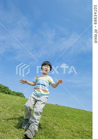 公園の丘を下る男の子 68634105