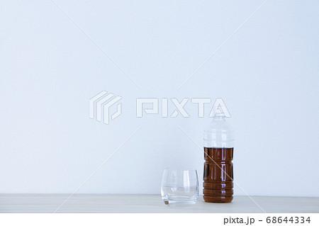 お茶の入ったペットボトルと空のグラス 68644334