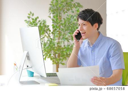 パソコン画面を見て驚く電話中のビジネスマン 68657058