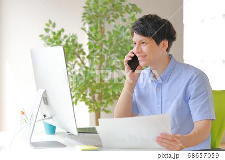 パソコン画面を笑顔で見る電話中のビジネスマン 68657059