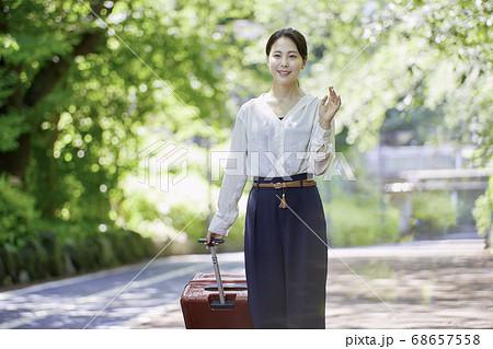新緑の中スーツケースを持つ若い女性 68657558