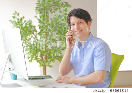 カメラ目線の笑顔で電話するビジネスマン 68661315