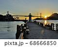朝焼けの空を背景に、日の出の光を浴びた関門橋とあるかぽーと波止の紅白の灯台 68666850