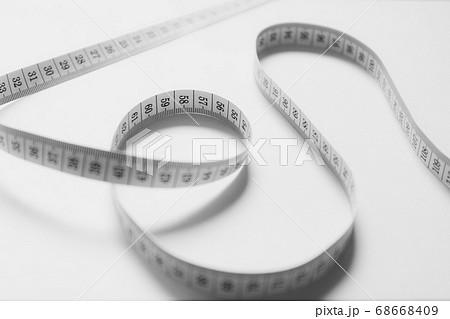 ランダムな形に置かれた巻尺 モノクロ 68668409