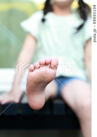 濡れ縁で座って足を伸ばして遊ぶ女の子 68693198