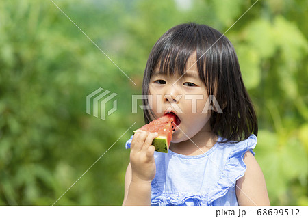 畑で採れた新鮮なスイカを食べる子供 68699512