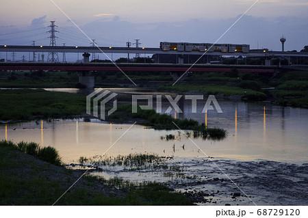 多摩川を渡る多摩モノレールと夕景 68729120