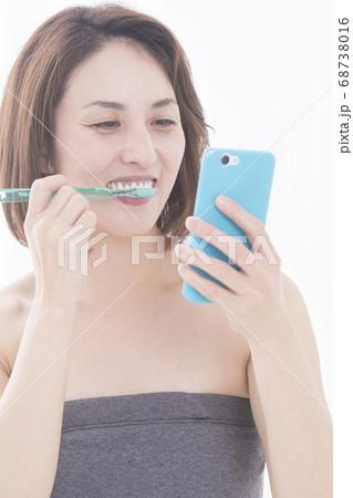 歯磨きをしながらスマホを見る女性 68738016