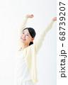 両手を上げる笑顔の若い女性 68739207