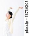 両手を上げる笑顔の若い女性 68739208