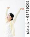 両手を上げる笑顔の若い女性 68739209