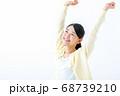両手を上げる笑顔の若い女性 68739210