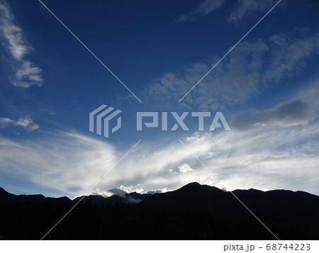 不思議な雲と青空と逆光で黒く見える山 68744223