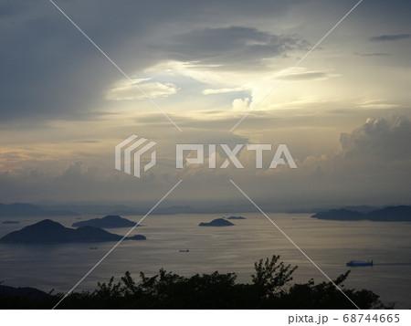 不思議な空と静かな瀬戸内海の島々と船のある景色 68744665