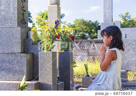 お墓参り 墓前で手を合わせて黙とうする女の子 68756037