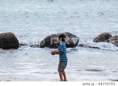 夏休みの思い出 海岸で波と戯れる少年 68759703