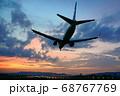 夕暮れの中を飛ぶ飛行機 68767769
