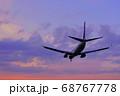 夕暮れの中を飛ぶ飛行機 68767778