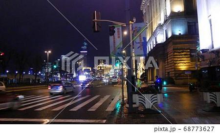 雨上がりの夜の路面に映る青信号とテールライト。目の前には横断歩道 68773627