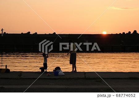 夕暮れの港で堤防釣りをする子供と母親 68774052