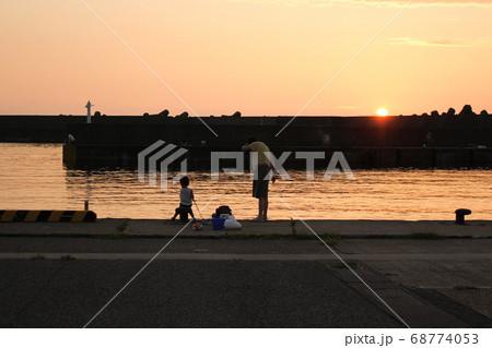 夕暮れの港で堤防釣りをする子供と母親 68774053