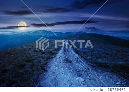 mountain road through grassy meadow at night. 68776475