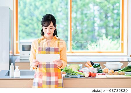 キッチンでタブレットを操作するミドルの女性 68786320