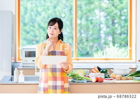 キッチンでタブレットを操作するミドルの女性 68786322