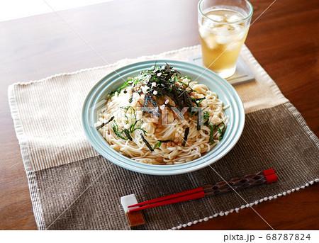 テーブルに置かれた、夏にぴったりの冷たいおろし納豆うどんと麦茶 68787824
