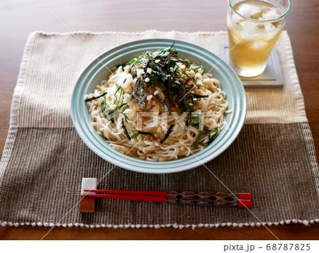 テーブルに置かれた、夏にぴったりの冷たいおろし納豆うどんと麦茶 68787825