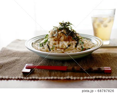 テーブルに置かれた、夏にぴったりの冷たいおろし納豆うどんと麦茶 68787826