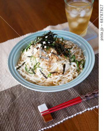テーブルに置かれた、夏にぴったりの冷たいおろし納豆うどんと麦茶 68787827