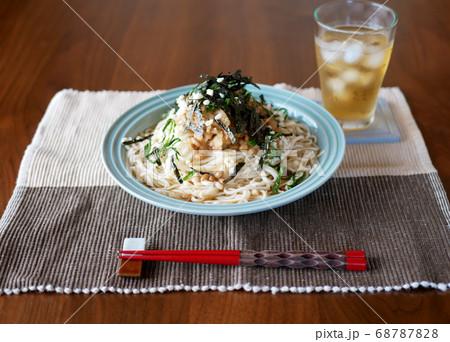 テーブルに置かれた、夏にぴったりの冷たいおろし納豆うどんと麦茶 68787828