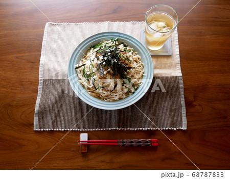 テーブルに置かれた、夏にぴったりの冷たいおろし納豆うどんと麦茶 68787833