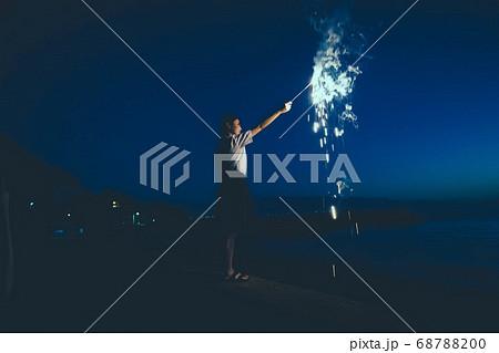 夜の海で花火をする女性 68788200