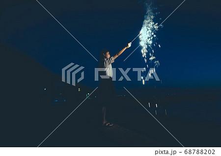 夜の海で花火をする女性 68788202