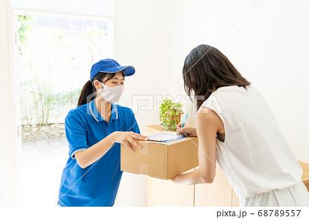 荷物を届ける宅配便の女性ドライバー 68789557
