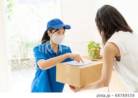 荷物を届ける宅配便の女性ドライバー 68789559