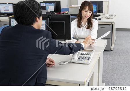 オフィースで仕事の内容を教えてもらう若い女性 68795312