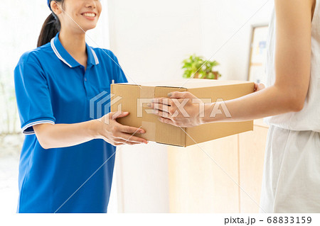 荷物を届ける宅配便の女性ドライバー 68833159