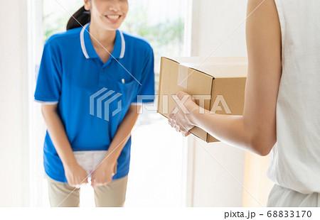 荷物を届ける宅配便の女性ドライバー 68833170