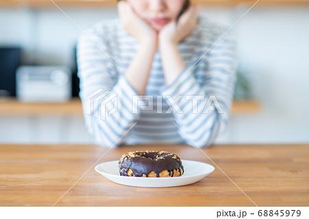 ドーナツを我慢するダイエット中の若い女性 68845979