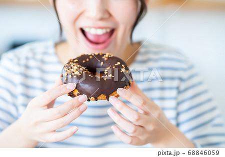 家でドーナツを食べる若い女性 68846059