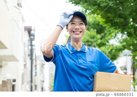 荷物を届ける宅配便の若い女性ドライバー 68860331